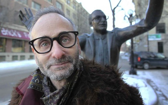 Alon Nashman  next to the statue of John Hirsch in front of the Manitoba Theatre Centre, image from Winnipeg Free Press